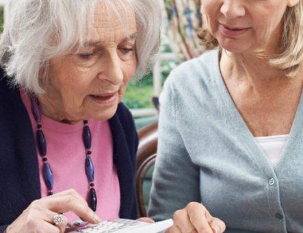 two women look over some bills