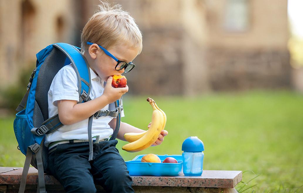 A cute boy at school eating fruit