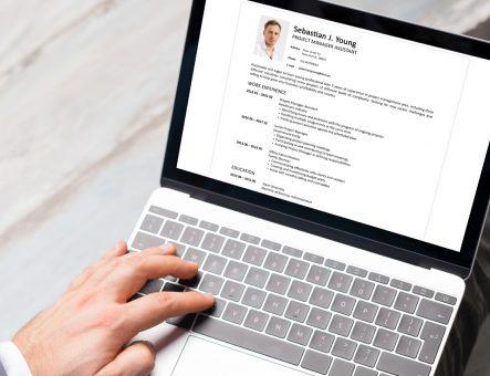 Man writing a CV on a laptop