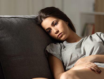A woman with depression slumps on a sofa